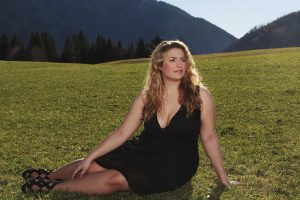 098507d8d221 Blonde elegant woman with oversize half lying in black dress and wide  neckline on a meadow