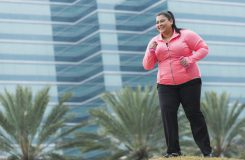 An overweight Hispanic woman in her 30s exercising with handweights outdoors. In the background out of focus is a building., She is smiling, looking away from the camera.